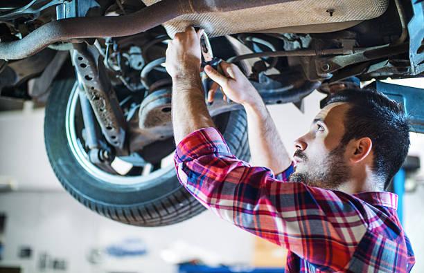 Mécanicien travaillant sous voiture, un véhicule à l'atelier. - Photo