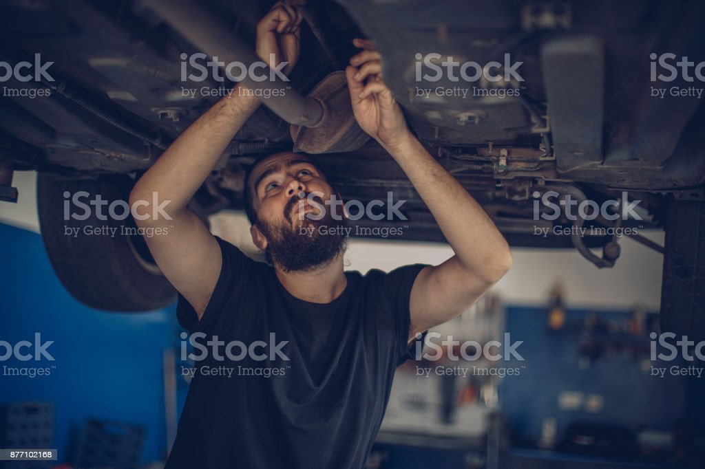 Car mechanic working under a vehicle at workshop stock photo