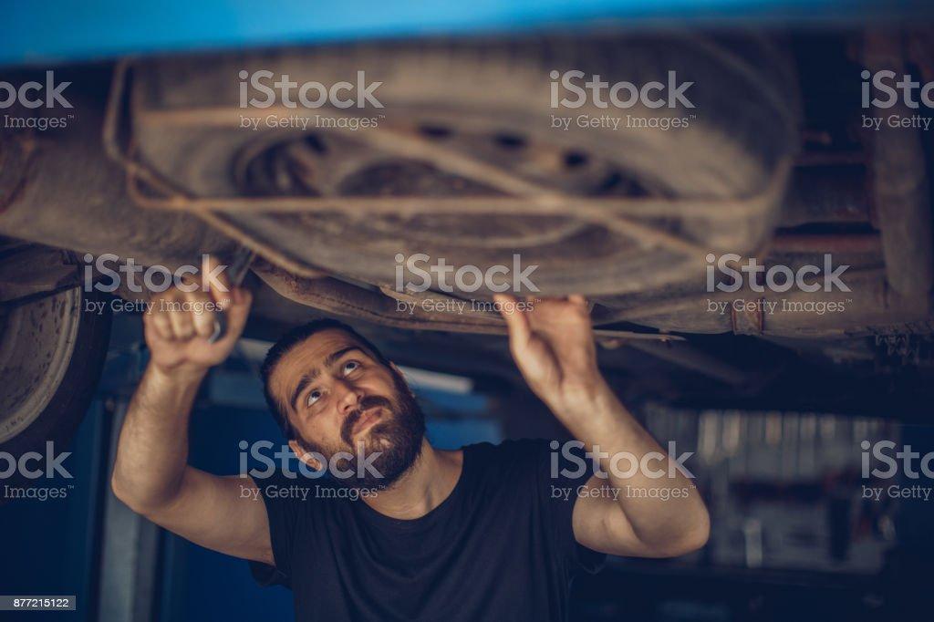 Car mechanic working under a vehicle stock photo