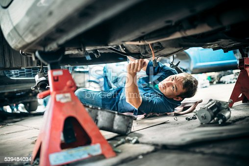 Low angle view of a mechanic working under a vehicle.