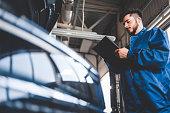 istock Car mechanic writes repair plan on clipboard. Auto service worker male 1254065829