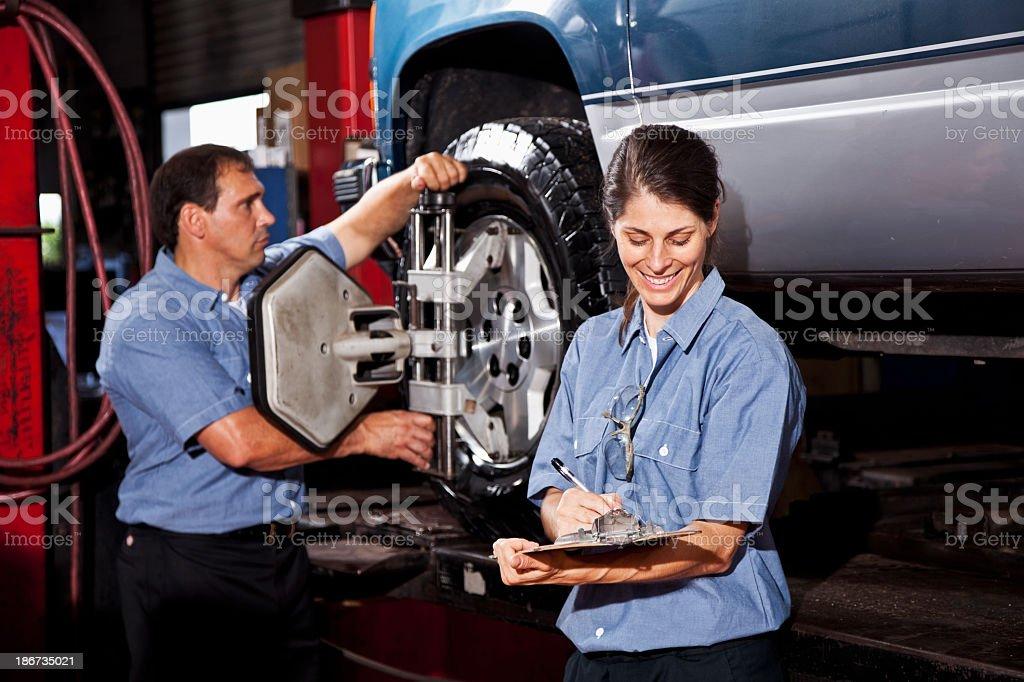 Car mechanics performing wheel alignment stock photo