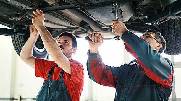 Car mechanics. Closeup front view of two car mechanics working under a vehicle that is being serviced. They are aged 30 and 50 and have been working together for the last five years. socket wrench stock pictures, royalty-free photos & images