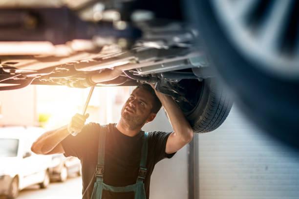 kfz-mechaniker unter dem fahrzeug reparieren automobile in seiner werkstatt. - autowerkstatt stock-fotos und bilder