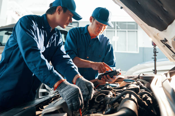 Car mechanics working with multimeter stock photo