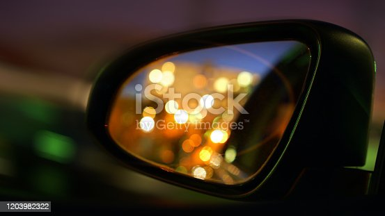 istock car mirror with headlight reflection of vehicle at night 1203982322
