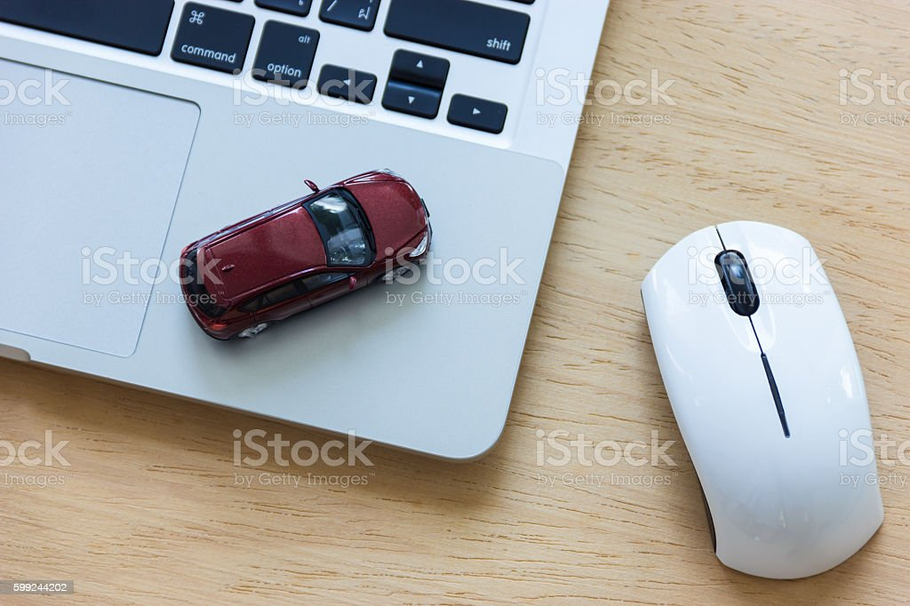 Car model on notebook and mouse on wooden desk - Lizenzfrei Auto Stock-Foto
