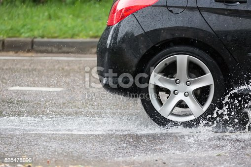 istock Car motion through big puddle of water splashes from the wheels on the street road. 825478696