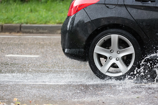 Car motion through big puddle of water splashes from the wheels on the street road.