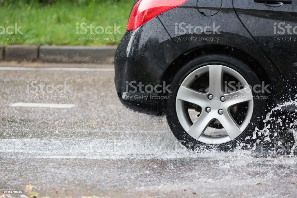 Movimiento del coche a través del Charco de agua salpicaduras de las ruedas en el camino de la calle. - foto de stock