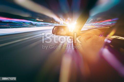 157590217 istock photo Car moving fast at night 599471070