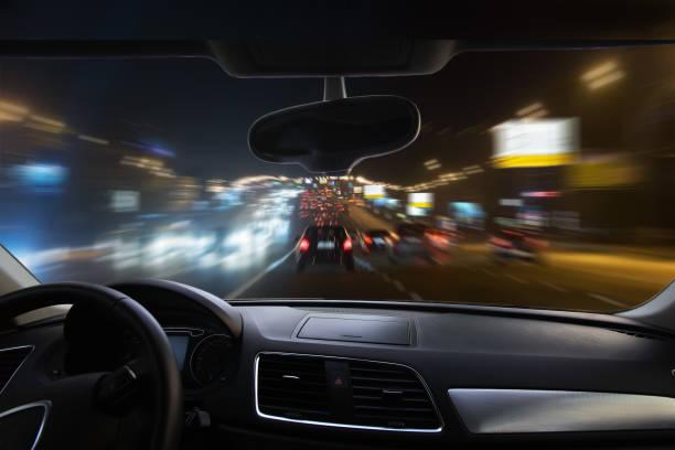 voiture se déplaçant sur la route de nuit - voiture nuit photos et images de collection