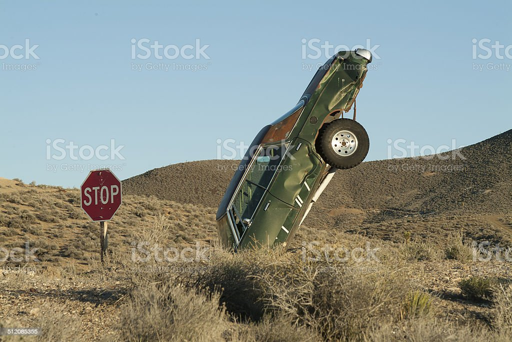 Car nosediving/crashing into desert floor behind a stop sign stock photo