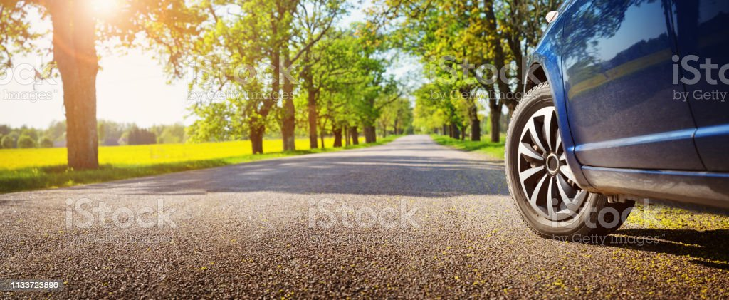 Car on asphalt road in summer Car on asphalt road on summer day at park Alley Stock Photo