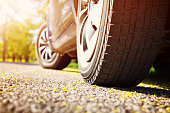Car tires closeup on asphalt road on summer day at park. Vehicle outdoors in nature with beautiful sunlight. Transportation, vacations and travel conceptCar on asphalt road on summer day at park