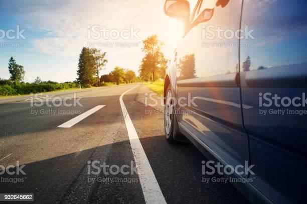 Car on asphalt road on summer day at park. Automobile on highway