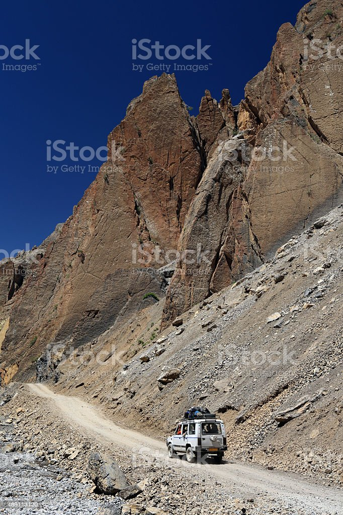 4WD Car on dirt road beside high rock mountain, India stock photo