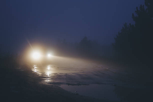 Car on dirty road in strong haze fog at twilight Car on dirty road in strong haze fog at twilight headlight stock pictures, royalty-free photos & images