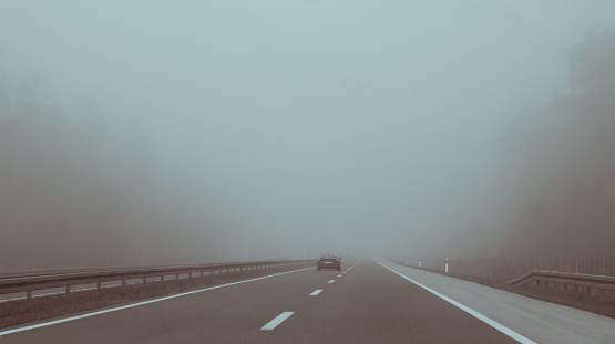 Car on highway entering fog, vanishing in the distance
