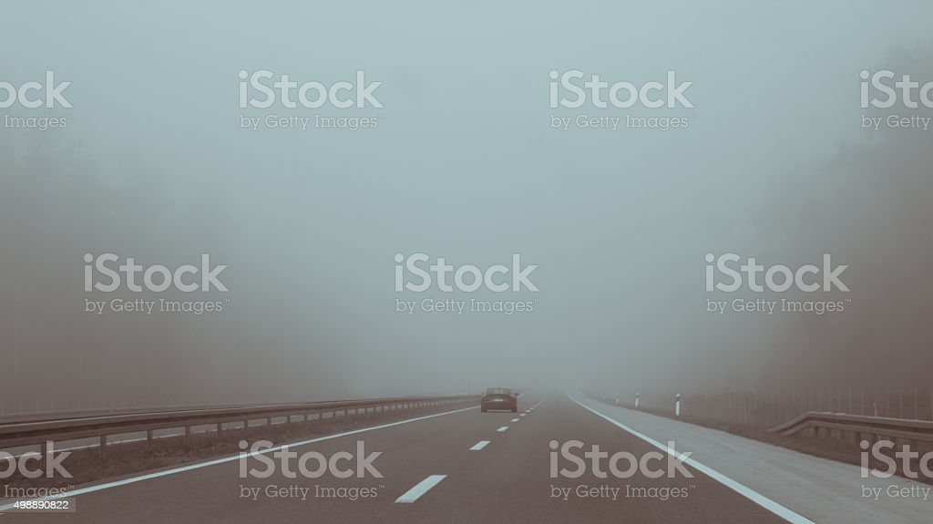 Car on highway entering fog, vanishing in the distance stock photo