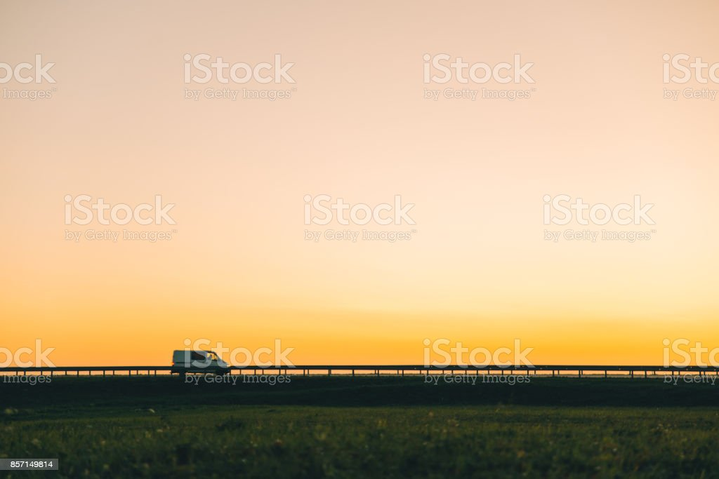 car on highway on sunset stock photo