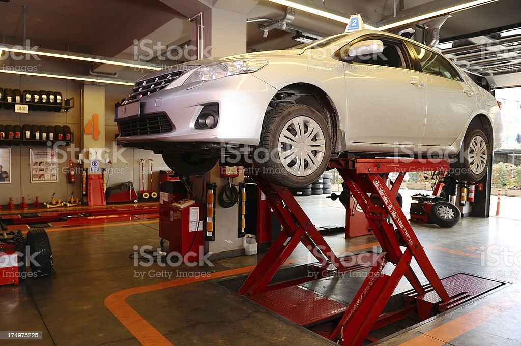 Car on lift in a repair garage stock photo