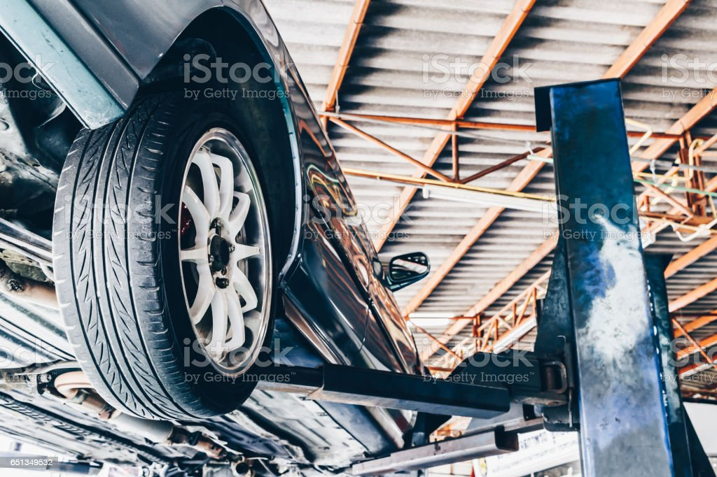 car on lift in car repair station stock photo
