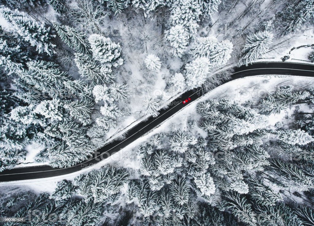 Car on road in winter trough a forest covered with snow stock photo