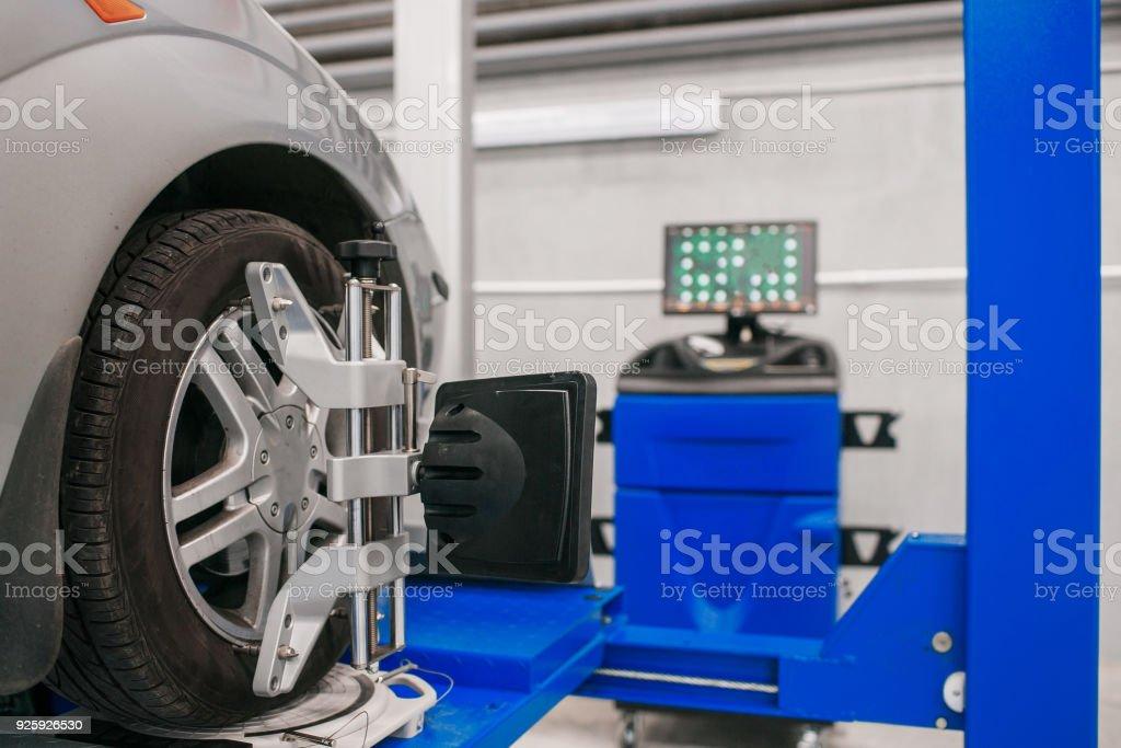 Carro carrinho com rodas de sensores para verificação da cambagem alinhamento na oficina da estação de serviço. - foto de acervo