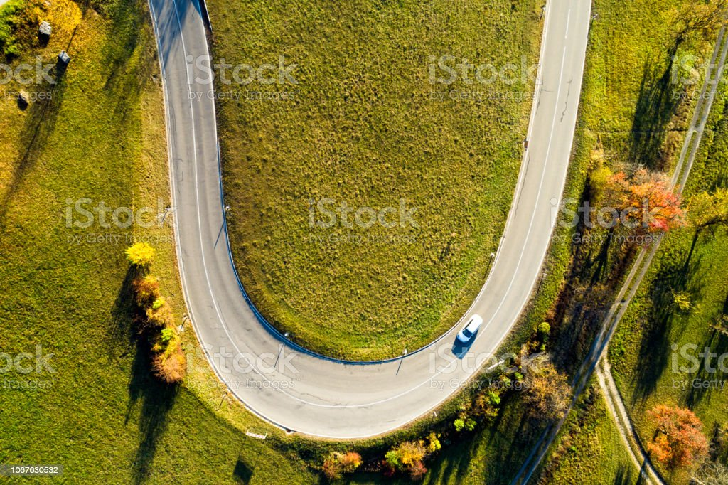 Car on the bend of the road in autumn, aerial view.