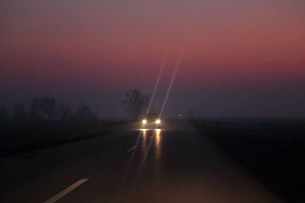 car on the night road at the sunset - mist donker auto stockfoto's en -beelden