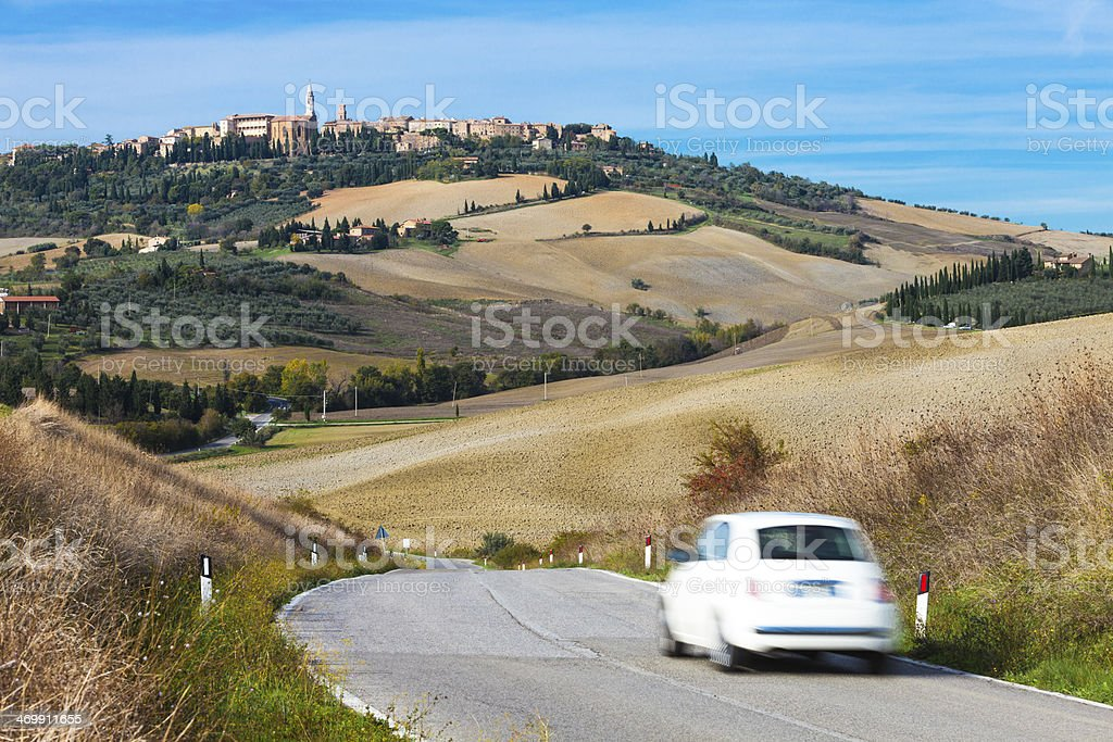 Car on Winding Road, Pienza in Background, Tuscany, Italy royalty-free stock photo