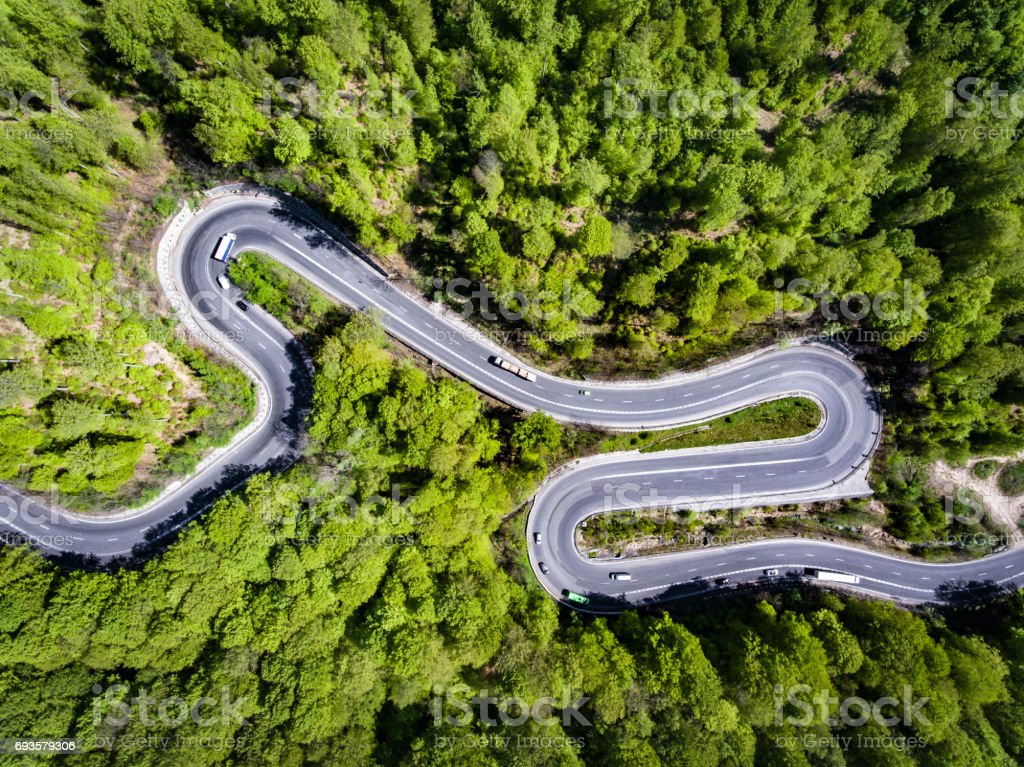 Car on winding road trough the forest, Transilvania, Romania stock photo