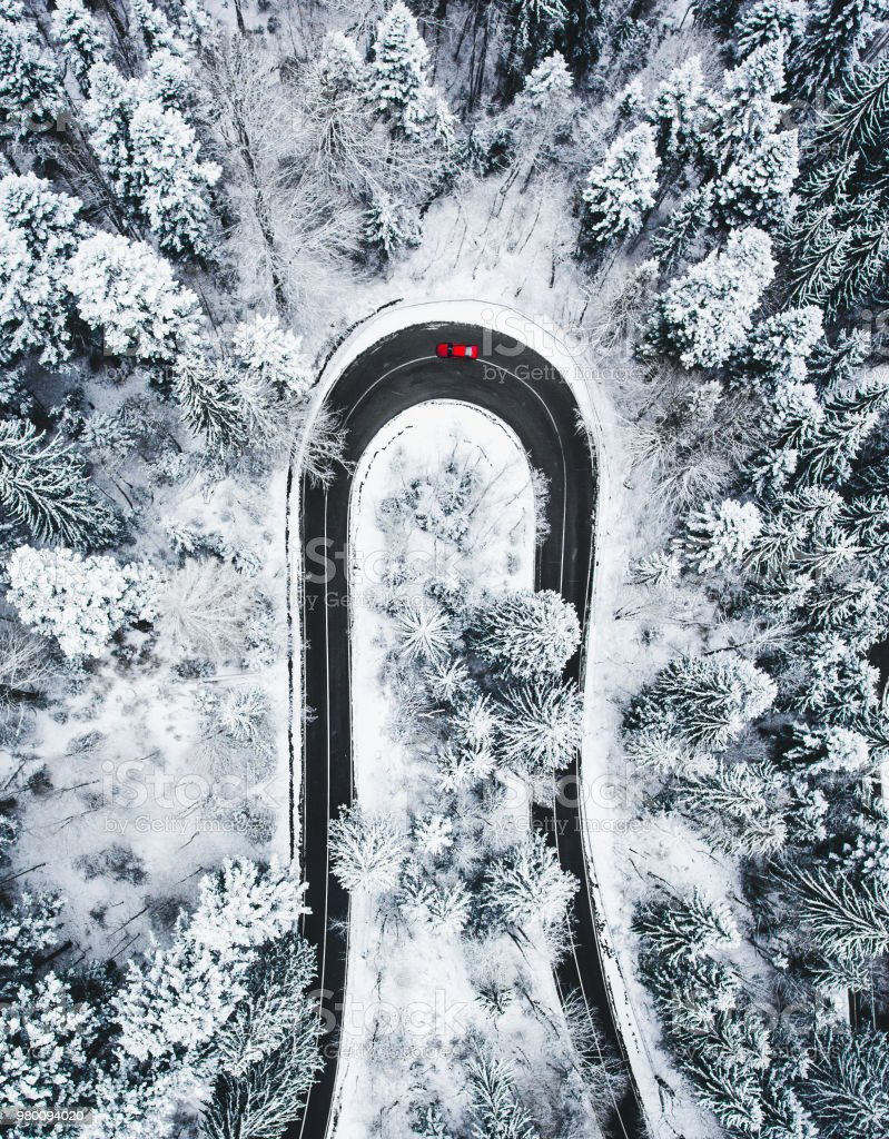 Car on winding winter road as seen from above stock photo