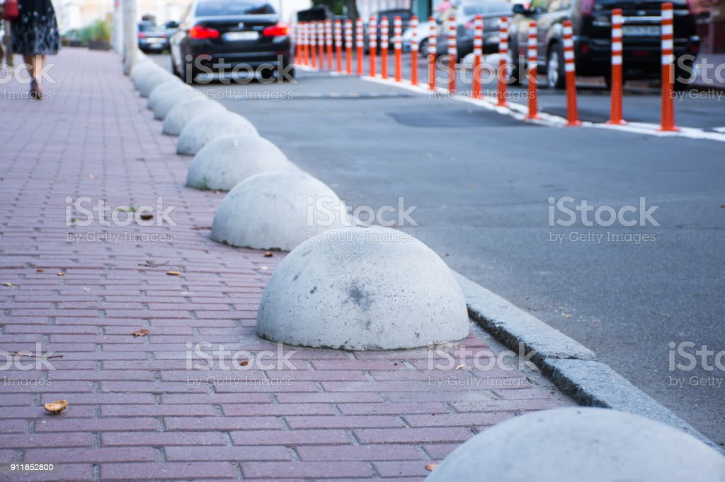 Car or motor vehicle stop security barriers or hemispheres bollards. Concrete structures to prevent parking on the sidewalks are placed at the edge of the roadway for cars stock photo