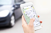 istock Car or ride share mobile app in smartphone. Carsharing, ridesharing or carpool service. Sharing economy concept. Person ordering taxi online with phone. Map location in screen. 1209272515