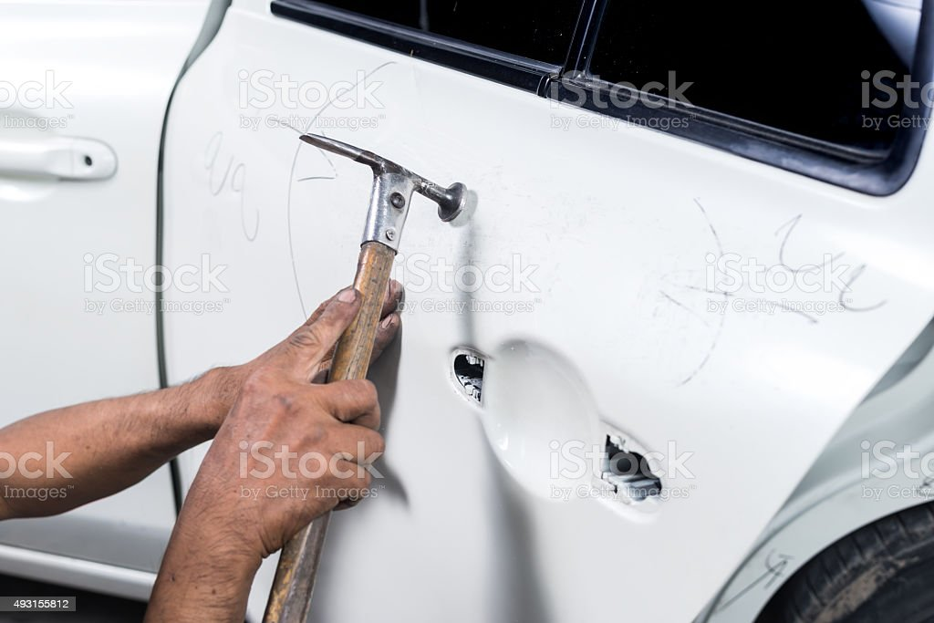 Car paint repair series : Worker repairs white car paint stock photo