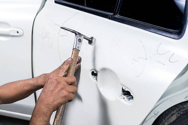 Car paint repair series : Worker repairs white car paint stock photo
