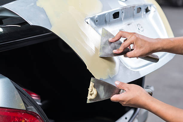 Car paint repair series : Working on putty stock photo