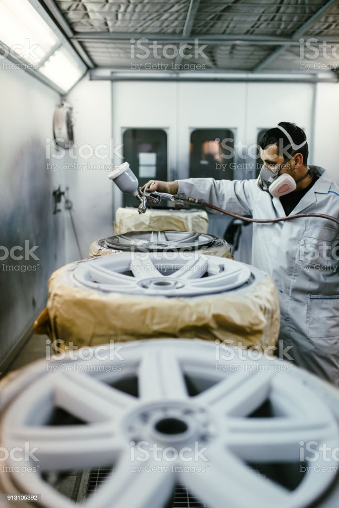 Man with protective clothes and mask painting car parts using spray...