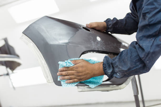 Car painting Male worker preparing car for painting. He is cleaning car parts with rag. lacquered stock pictures, royalty-free photos & images