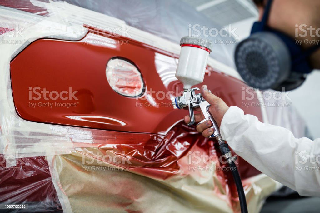 Man with protective clothes and mask painting car using spray...
