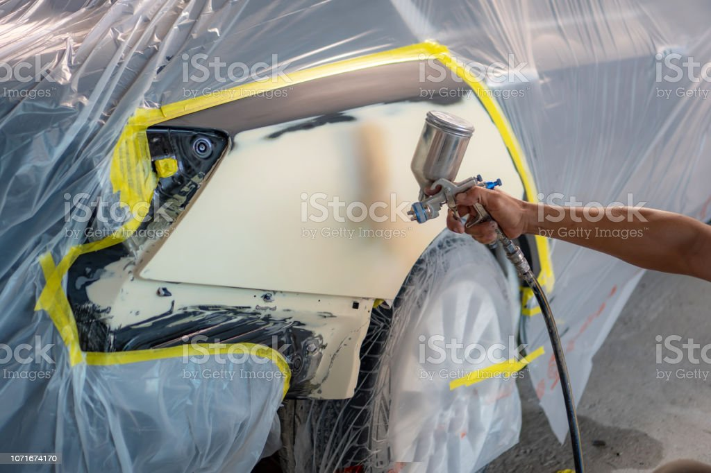 Repairing car body by puttying close up work after the accident by...