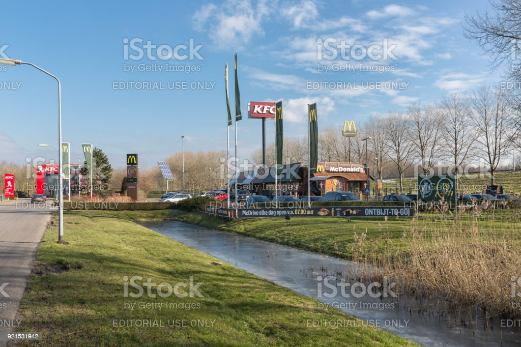 Car park near Dutch motorway with fastfood restaurants stock photo