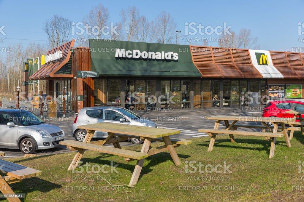 Car park near Dutch motorway with Mc Donald's fastfood restaurant stock photo