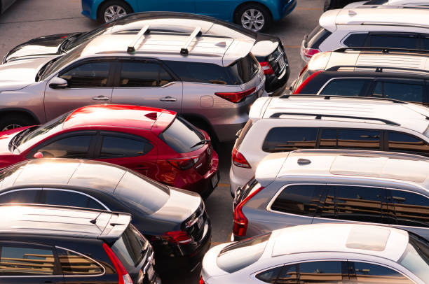 car parked at concrete parking lot. aerial view of car parking area of the mall. automotive industry. automobile parking space. global automobile market concept. - used car selling stock pictures, royalty-free photos & images