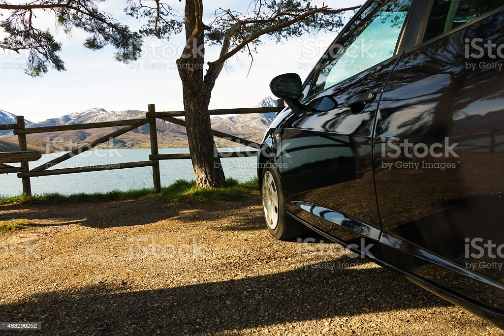 Car Parked in front of Landscape Water and Mountains stock photo