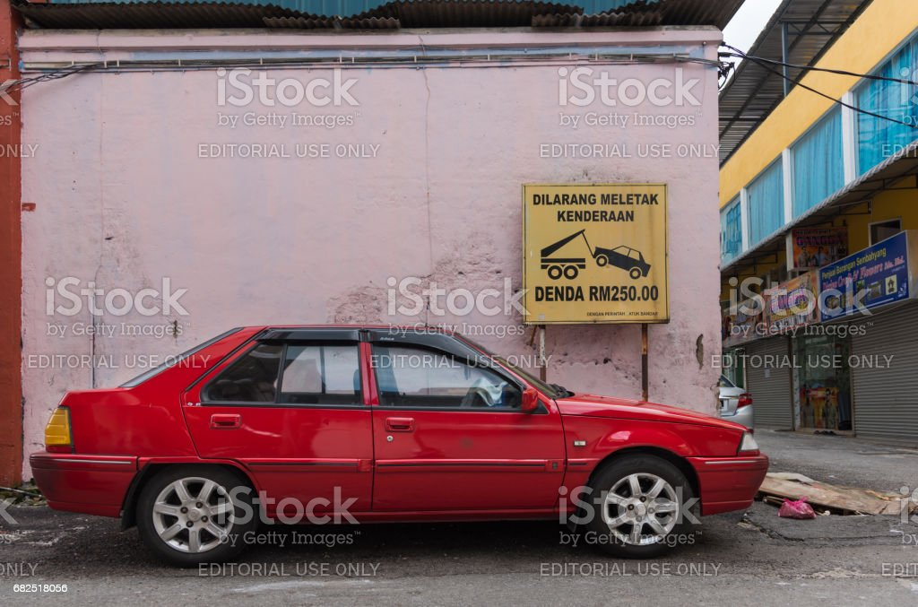 Car Parked in front of tow-away sign stock photo