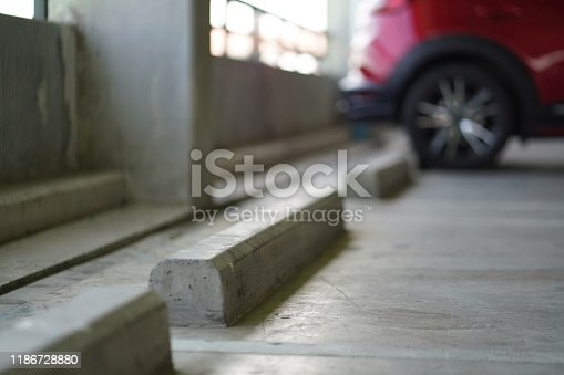 istock Car parking lots at office/business tower. 1186728880