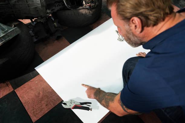 car parts shop owner warehouse checking blueprint concept - grafik design tattoos stock-fotos und bilder